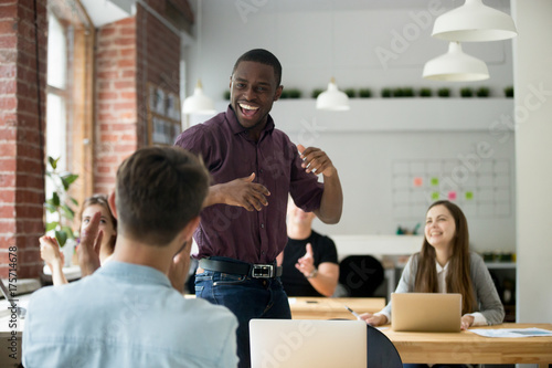 Fotografía  African american office worker dancing surrounded by colleagues