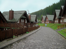 Wooden Cottages Are At Mountain Resort Near Forest Under Blue Sky