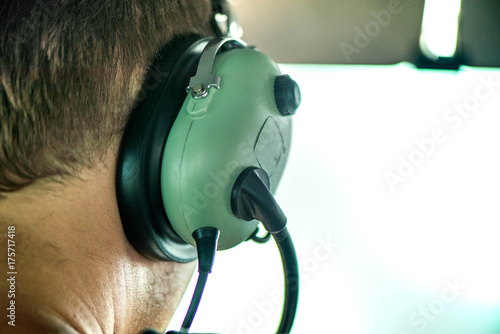 Fotografie, Obraz Macro shot of pilot wearing aviation headset and flying with small plane and talking with dispatcher