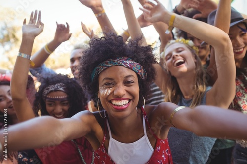 Cheerful young woman enjoying at music festival - 175727883