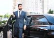 Handsome man in suit getting out of car