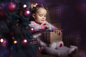 Baby girl sitting in a chair near a Christmas tree. Girl holding a gift, she tries to open it