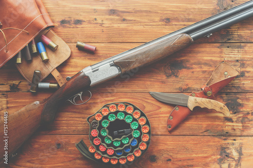 Poster Jacht Hunting equipment. Shotgun, hunting cartridges and hunting knife on wooden table.
