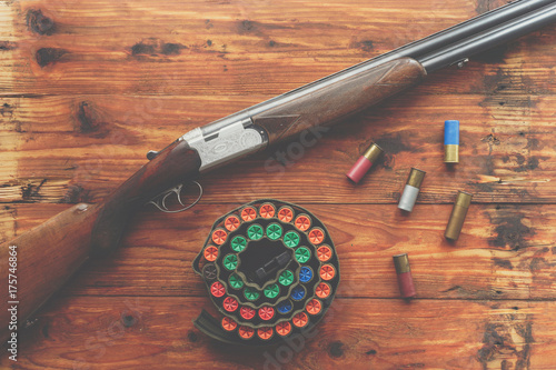 Foto op Canvas Jacht Hunting equipment. Shotgun and hunting cartridges on wooden table.