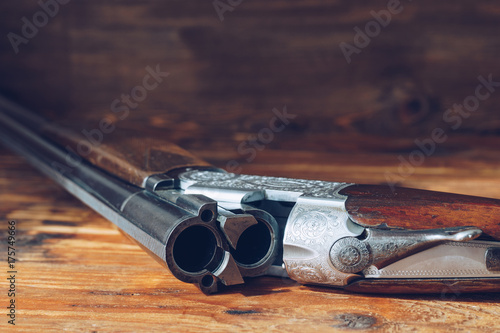 Open hunting rifle isolated on wooden background Canvas Print