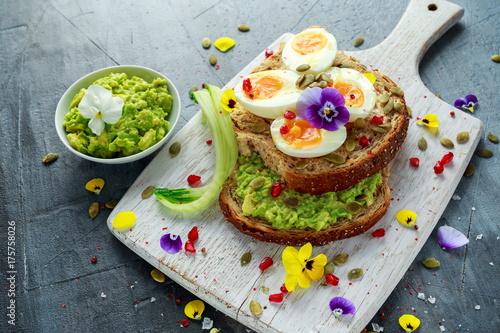 Zdjęcie XXL Smaczne kanapki z awokado jajka na twardo, nasion dyni i jadalne kwiaty viola w białej tablicy. zdrowe jedzenie