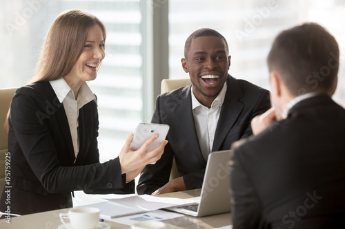 Photo  Happy smiling caucasian businesswoman using digital tablet at negotiations with multinational partners, laughing at joke on meeting