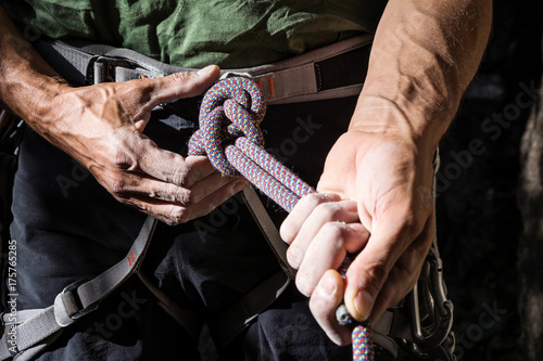 Foto op Plexiglas Alpinisme mountain climber tying rope in double bowline knot