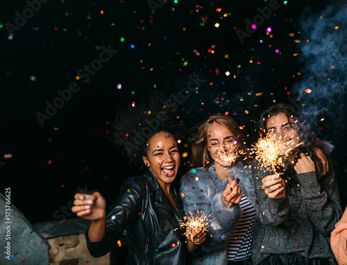 Fotografía  Group of happy friends celebrating new year's eve with confetti and sparklers