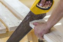 Carpenter Hand With Saw Cuttin...