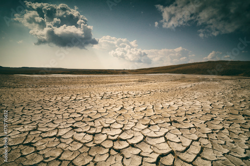 Fotografie, Tablou dramatic sky with clouds over cracked earth