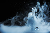 Boiling water splash with steam on black background closeup