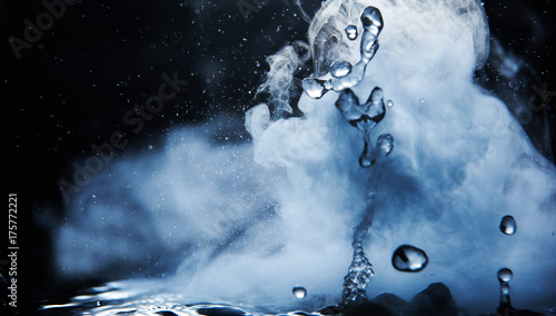 Boiling water splash with steam on black background closeup Canvas Print