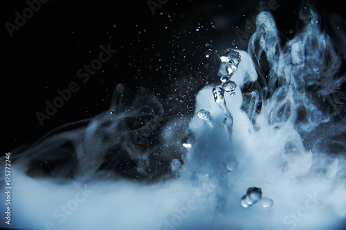 Fotografering  Boiling water splash with steam on black background closeup