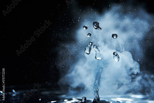 Fotografija  Boiling water splash with steam on black background closeup