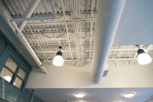 Staande foto Industrial geb. Close up on light and pipes on the ceiling interior