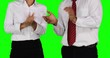 Two unrecognizable business team applauding together while standing in the studio with green screen background. Shot in 4k resolution