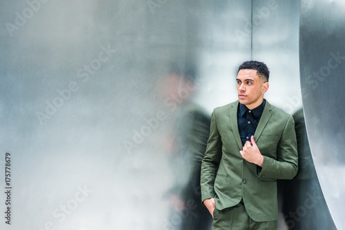 Foto op Plexiglas Artist KB Portrait of young American Businessman in New York, wearing green suit, black undershirt, hand on front, standing by sliver metal wall, looking away, thinking. Color filtered with dart blue tint..