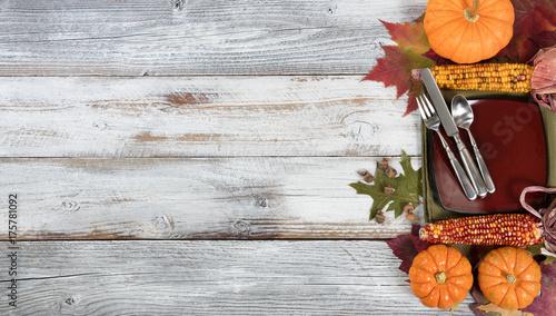 Plakat Podstawowe ustawienie kolacji z liści jesienią i inne dekoracje upadku na białym rustykalnym desek