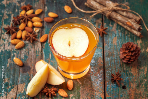 Fototapeta Hot drink of apple tea with cinnamon stick. Hot drink with apples for autumn or winter. obraz