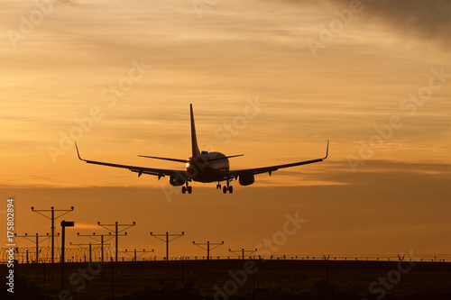 Commercial airliner lands in silhouette during a golden sunset. #175802894