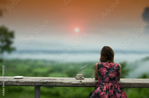 Fototapeta Kobiety odprawy. Piękna kawiarnia w leśnej mgle i drewnianym stole mglista góra i zachód słońca
