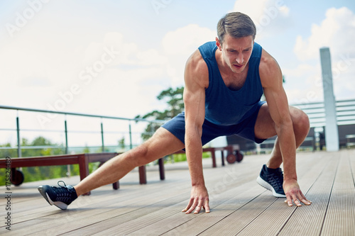 Fotografie, Tablou  Full length portrait of concentrated young runner stretching legs outdoors while