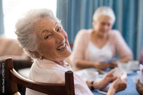 Fotomural Smiling senior woman playing cards with friends