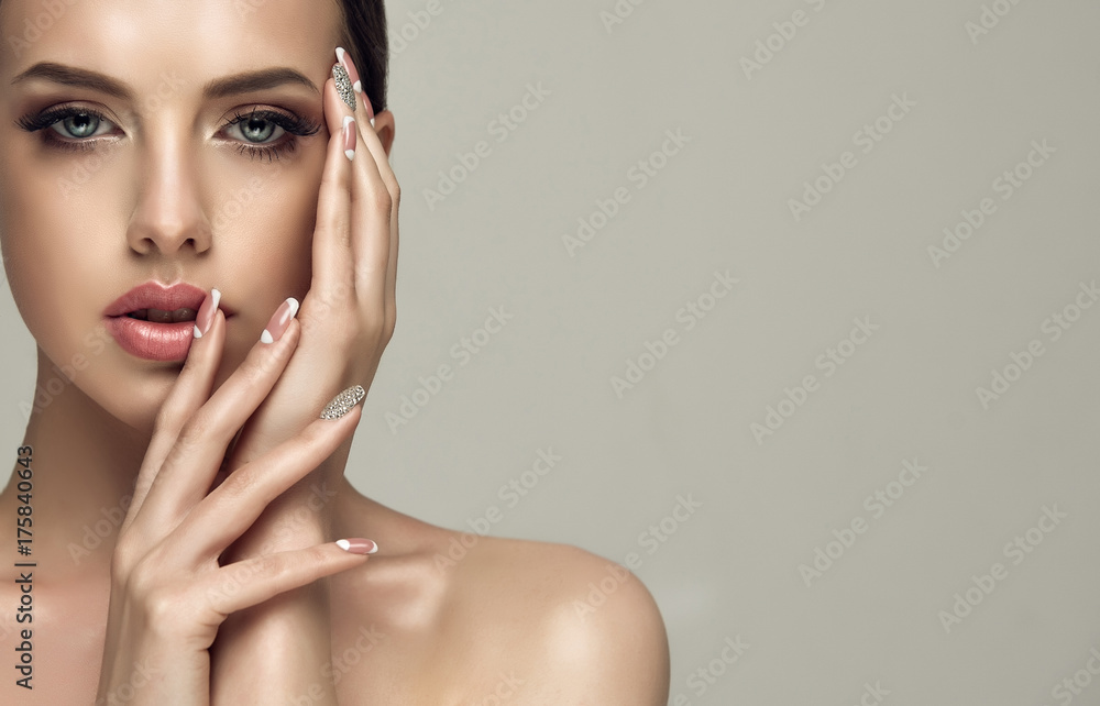 Fototapeta Beautiful model girl with a beige French manicure nail design with rhinestones . Fashion makeup and care for hands and nails and cosmetics
