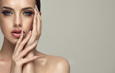 FototapetaBeautiful model girl with a beige French manicure nail design with rhinestones . Fashion makeup and care for hands and nails and cosmetics