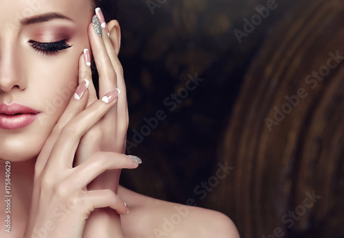 Tablou Canvas Beautiful model girl with a beige French manicure nail design with rhinestones