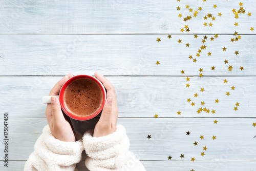 Poster Chocolate female hand holding cup of hot cocoa or chocolate on wooden table from above