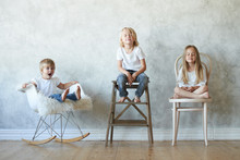 Horizontal Studio Shot Of Blonde Little Boy And Girl Meditating With Eyes Closed While Their Mischievous 5-year Old Sister With Short Hair Sitting Next To Them And Screaming In Shock, Distracting Them