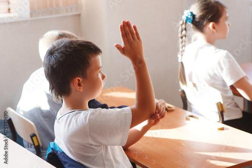 Plakat Szczęśliwy uczeń szkoły podstawowej podnosi rękę w klasie.