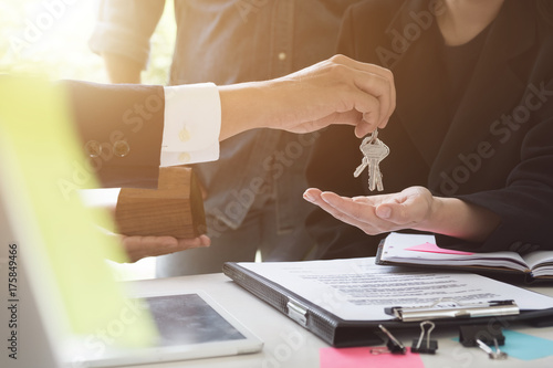 Photo  estate agent giving house keys to couple and sign agreement in office