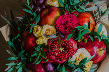 Fresh Autumn Vegetarian Fruity Bouquet Of Apples, Grapes, Pomegranates And Roses, With Green Leaves On A Dark Background