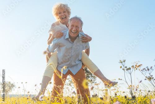 Photo  Senior Mann trägt seine Frau auf dem Rücken, er hat eine gesunde Wirbelsäule