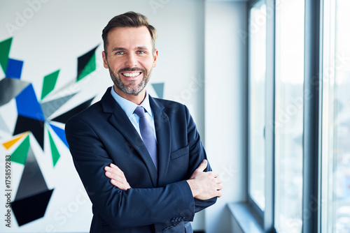 Fotografía  Businessman in office looking at camera with arms crossed
