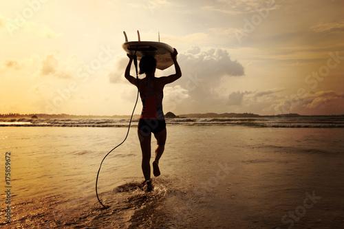 Plakat Tylni widok młoda kobieta surfingowiec z białym surfboard odprowadzeniem morze