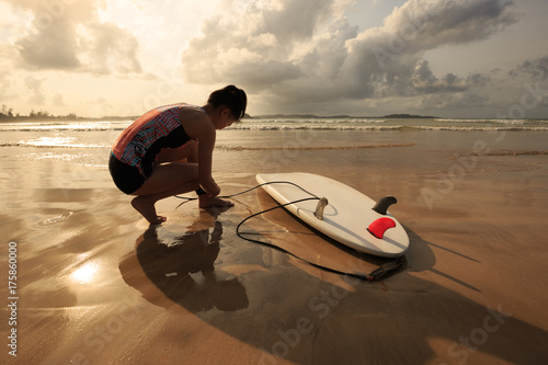 Plakat młoda kobieta surfer gotowy do surfowania na plaży