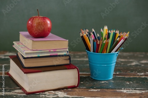 Fotografie, Obraz  Apple on stack of books with pen holder