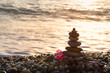 Pyramid of stones and red flower on the seashore