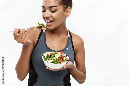 Keuken foto achterwand Kruidenierswinkel Healthy and Fitness concept - Beautiful American African lady in fitness clothes on diet eating fresh salad . Isolated on white background.
