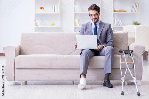 Fényképezés Businessman with crutches and broken leg at home working
