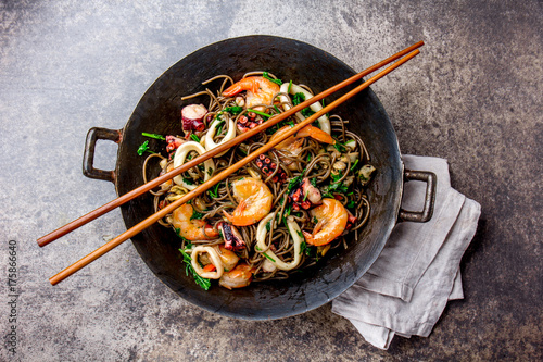 Buckwheat stir-fry noodles with seafood - shrimps, octopus, squid in cast iron asian wok with cooking chopstick Canvas Print