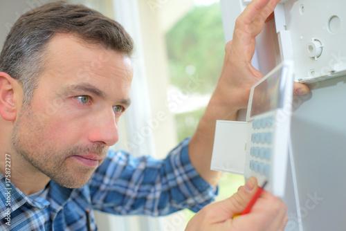 Man installing alarm keypad Canvas Print