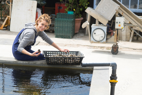 Photo oyster farmer cleans her produce