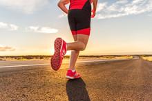 Running Shoes On Male Triathlete Runner - Closeup Of Feet Running On Road. Man Jogging Outside Exercising Training For Triathlon Ironman Outside At Sunset.