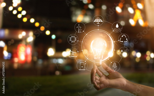 Obraz Hand holding light bulb in front of global, show the world's consumption with icons energy sources for renewable, Ecology concept. Elements of this image furnished by NASA. - fototapety do salonu