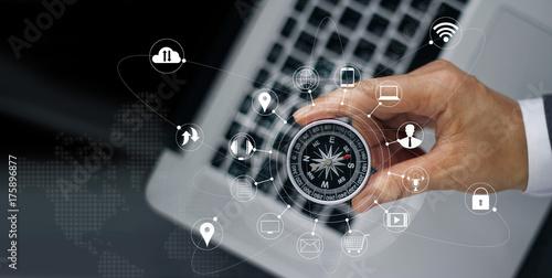 Fotografia  Biznesmen z kompasem trzymając w ręku na laptopa i ikona połączenia sieci klient